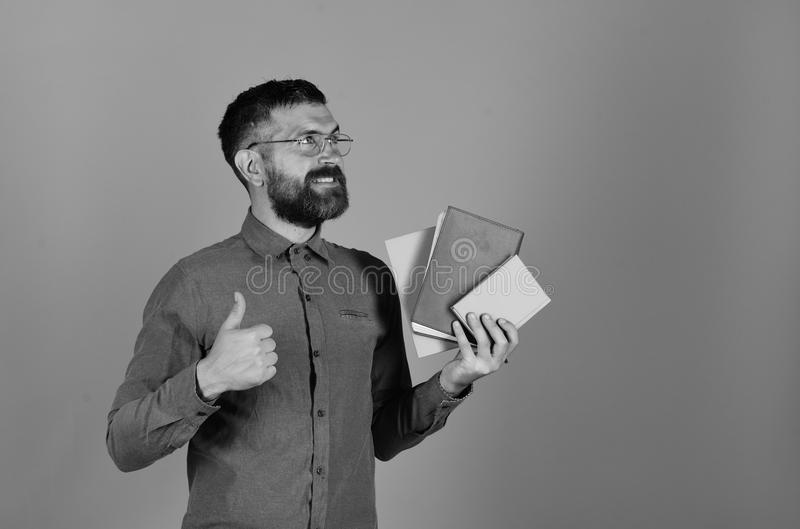 Profesor con los vidrios, el organizador y los pulgares para arriba Hombre con la barba y los libros Profesor con la expresión so fotografía de archivo libre de regalías