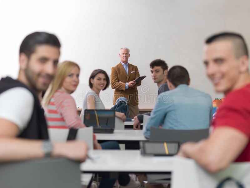 Profesor con un grupo de estudiantes en sala de clase imagen de archivo libre de regalías