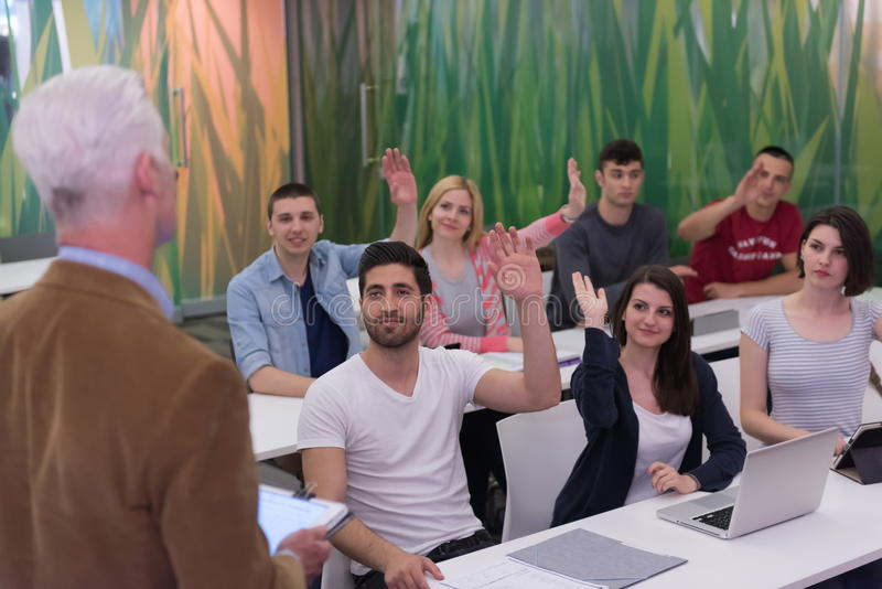 Profesor con un grupo de estudiantes en sala de clase imágenes de archivo libres de regalías