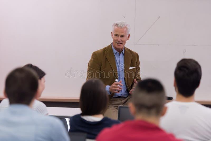 Profesor con un grupo de estudiantes en sala de clase imagen de archivo