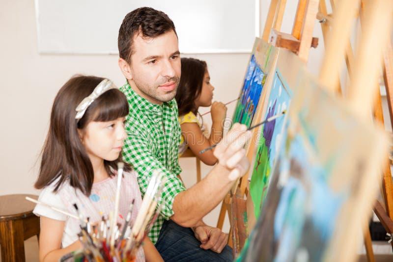Profesor de arte que ayuda a un estudiante imagenes de archivo