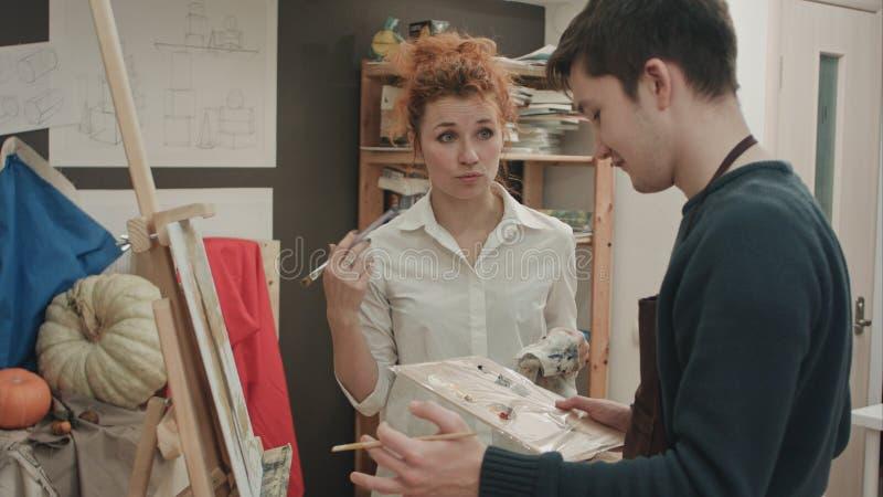 Profesor de arte de sexo femenino que analiza la pintura con su estudiante masculino foto de archivo