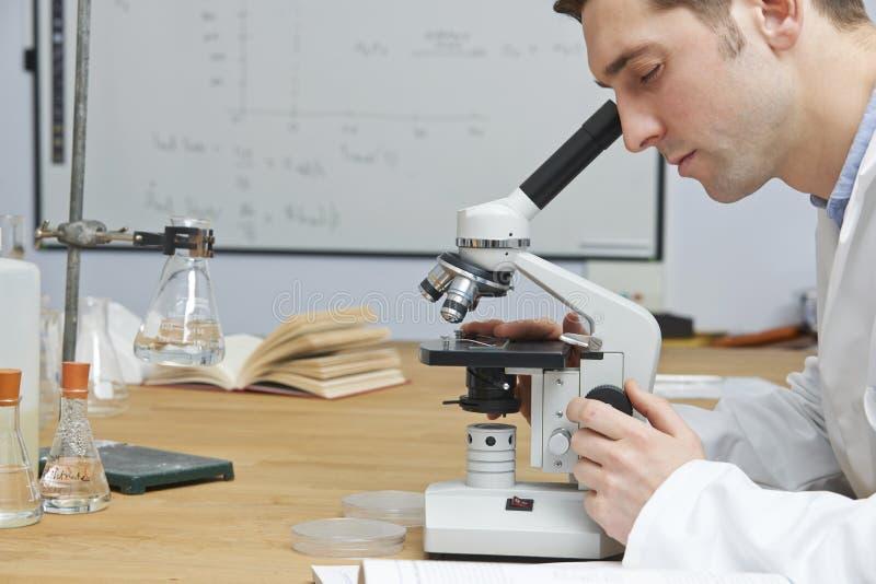 Profesor de biología de sexo masculino Looking Through Microscope en sala de clase fotos de archivo