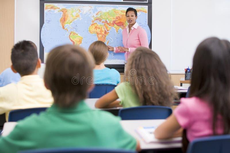 Profesor de escuela elemental en clase de la geografía foto de archivo