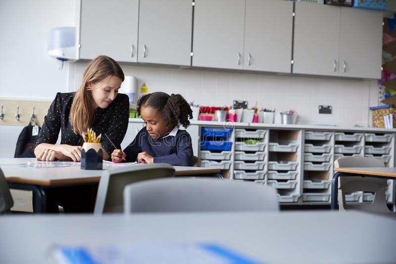 Profesor de escuela primario de sexo femenino joven que trabaja uno en uno con una colegiala que se sienta en la tabla en una sal imagen de archivo