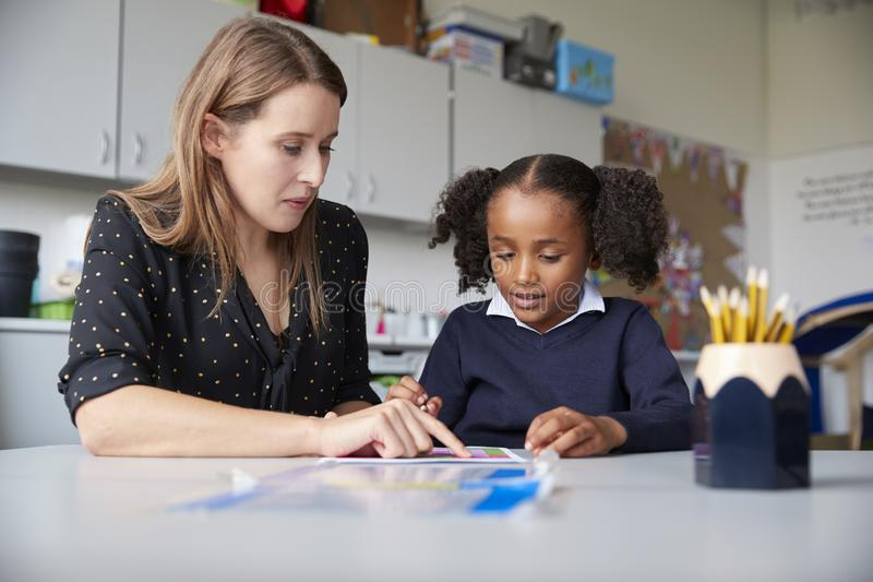 Profesor de escuela primario de sexo femenino joven que trabaja uno en uno con una colegiala en una tabla en una sala de clase, c imagen de archivo libre de regalías
