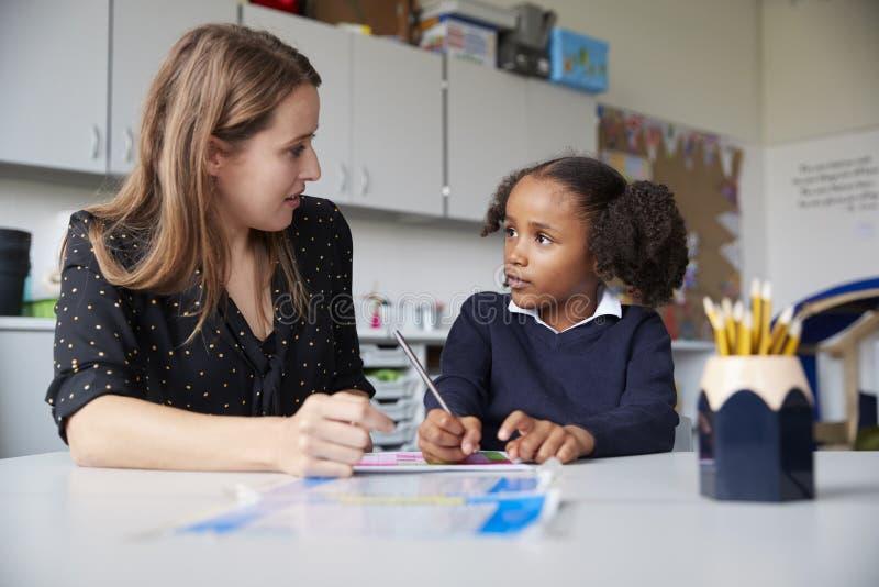 Profesor de escuela primario de sexo femenino joven que trabaja uno en uno con una colegiala en una tabla en una sala de clase, m foto de archivo