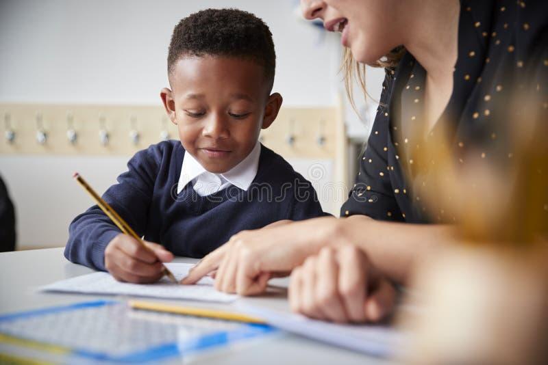 Profesor de escuela primario de sexo femenino que ayuda a un escolar joven que se incorpora en la tabla en una sala de clase, cie fotografía de archivo libre de regalías