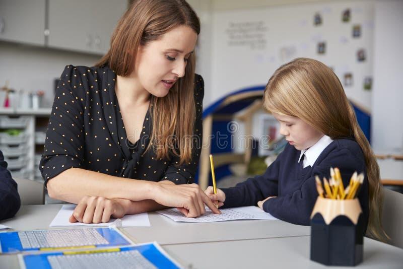 Profesor de escuela primario de sexo femenino que se sienta en una tabla en una sala de clase con una colegiala, ayudándole con s imagen de archivo libre de regalías
