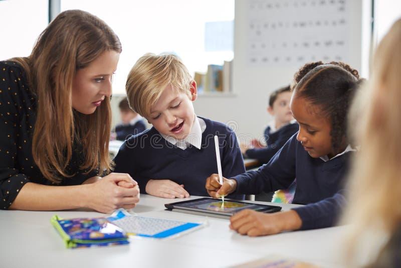 Profesor de escuela de sexo femenino que ayuda a dos niños usando una tableta en el escritorio en una sala de clase de la escuela foto de archivo libre de regalías