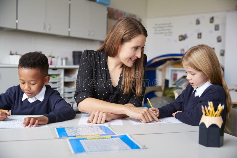 Profesor de escuela de sexo femenino que se sienta entre dos niños de la escuela primaria en una tabla en una sala de clase, ayud imagenes de archivo