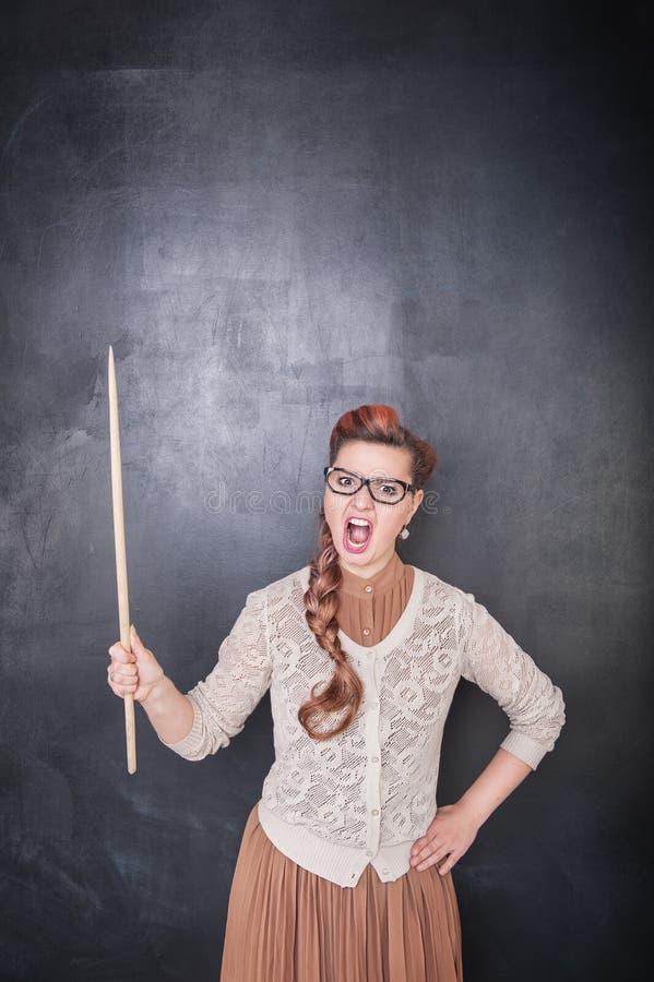 Profesor de griterío enojado con el indicador en el backgroun de la pizarra foto de archivo
