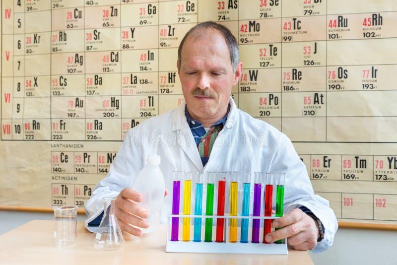 Profesor de la química que llena los tubos de ensayo coloridos foto de archivo