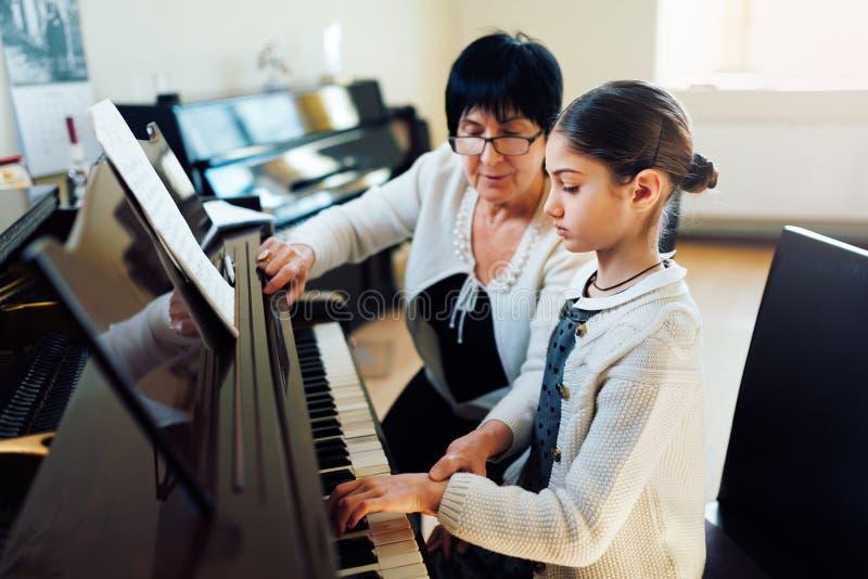 Profesor de música con el alumno en el piano de la lección fotos de archivo