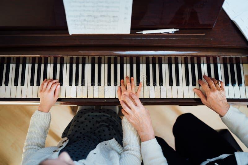 Profesor de música con el alumno en el piano de la lección, fotos de archivo libres de regalías