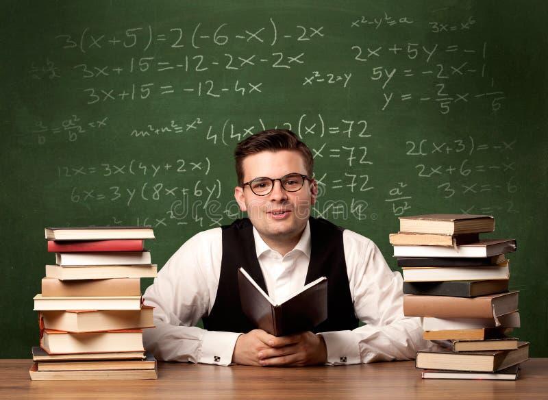 Profesor de matemáticas en el escritorio imagen de archivo libre de regalías