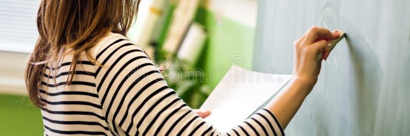 Profesor de sexo femenino joven o una fórmula de la matemáticas de la escritura del estudiante en la pizarra en sala de clase imágenes de archivo libres de regalías