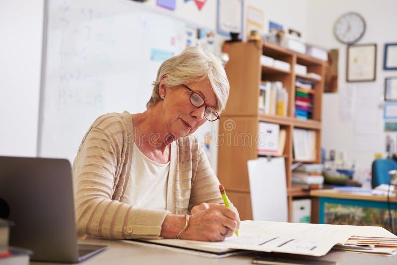 Profesor de sexo femenino mayor en su trabajo del ½ del ¿del studentsï de la marca del escritorio foto de archivo libre de regalías