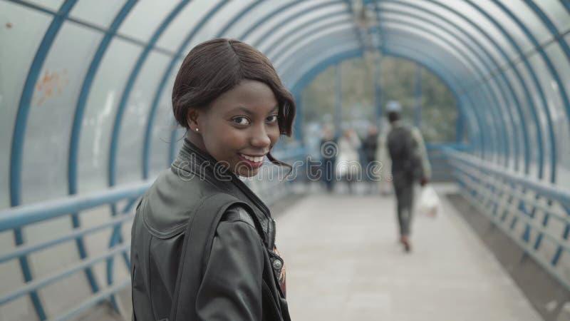 Profesor de sexo femenino negro joven con el peinado afro que lleva la pequeña cartera de la chaqueta de cuero, saliendo del edif fotografía de archivo libre de regalías