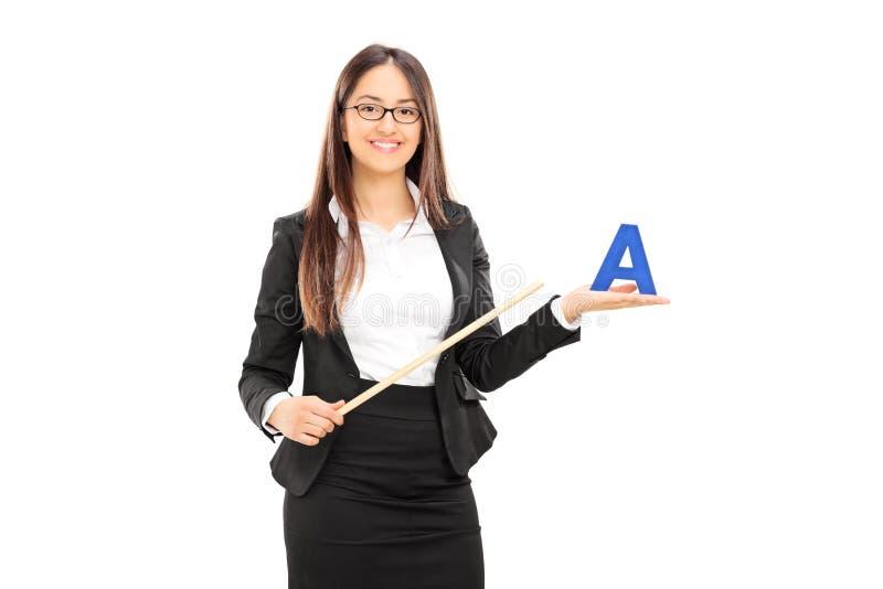 Profesor de sexo femenino que lleva a cabo un palillo y una letra imagen de archivo libre de regalías