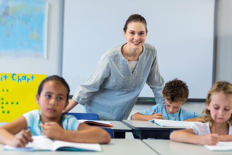 Profesor de sexo femenino sonriente con los niños foto de archivo