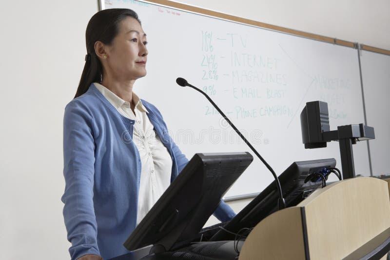 Profesor de sexo femenino Standing By Podium fotografía de archivo