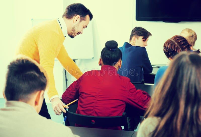 Profesor de sexo masculino que aclara el problema complicado al alumno durante examen fotos de archivo libres de regalías