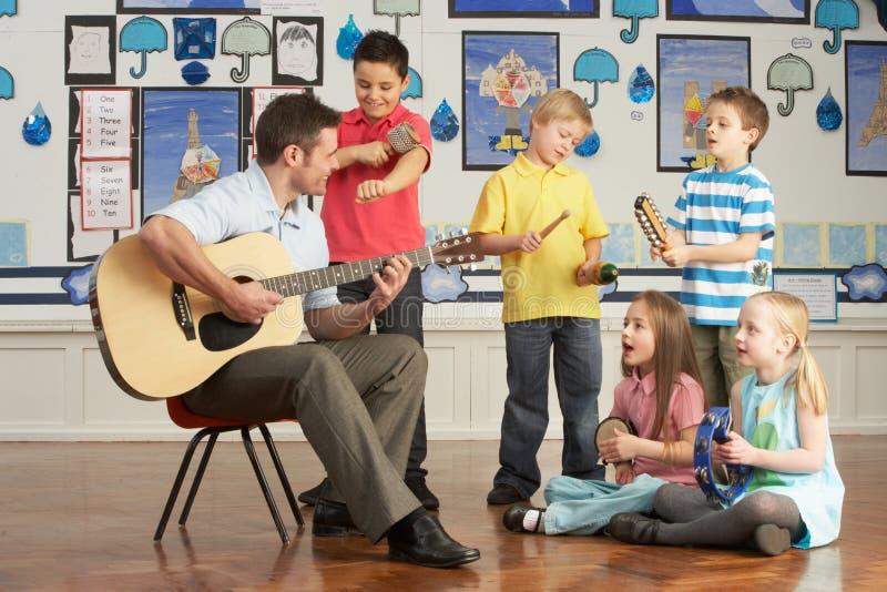 Profesor de sexo masculino que toca la guitarra con las pupilas foto de archivo libre de regalías