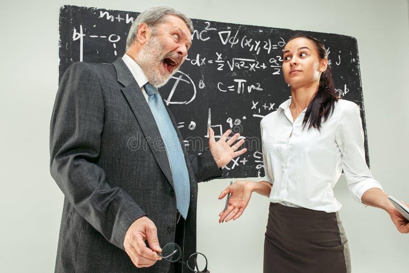 Profesor de sexo masculino y mujer joven contra la pizarra en sala de clase imagen de archivo