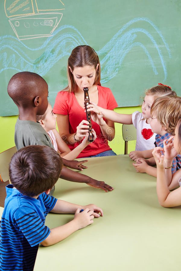 Profesor del cuarto de niños que toca la flauta foto de archivo libre de regalías