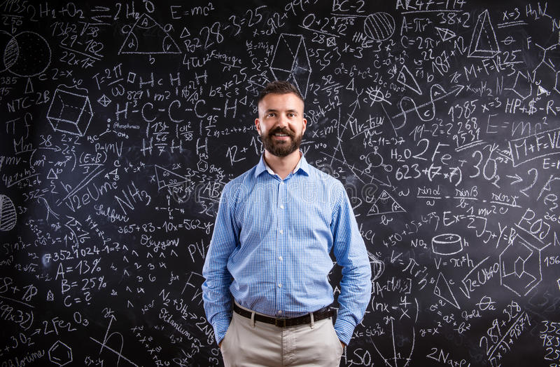 Profesor del inconformista contra la pizarra grande con símbolos matemáticos imagen de archivo libre de regalías