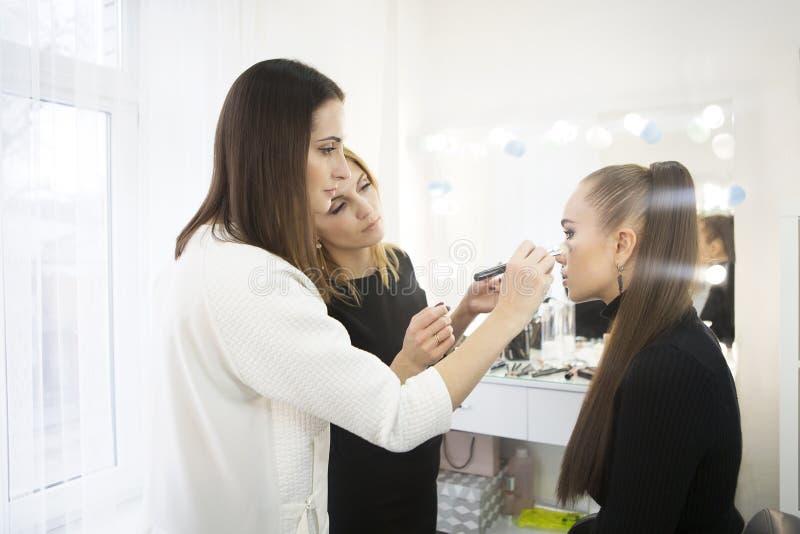 Profesor del maquillaje con su muchacha del estudiante Componga la lección preceptoral en la escuela de la belleza Componga el tr imágenes de archivo libres de regalías