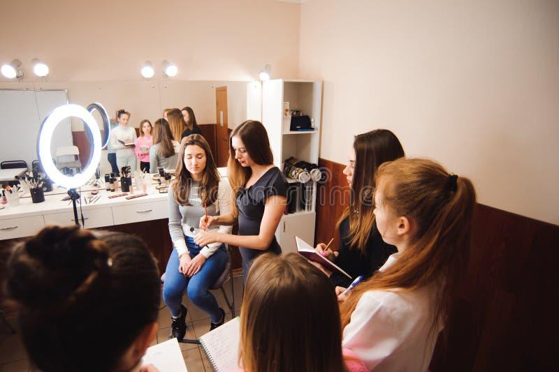 Profesor del maquillaje con sus muchachas del estudiante Lección preceptoral del maquillaje en la escuela de la belleza Clase pri imagen de archivo libre de regalías