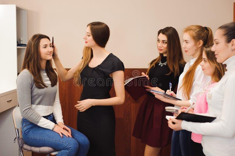 Profesor del maquillaje con sus muchachas del estudiante Lección preceptoral del maquillaje en la escuela de la belleza Clase pri fotografía de archivo