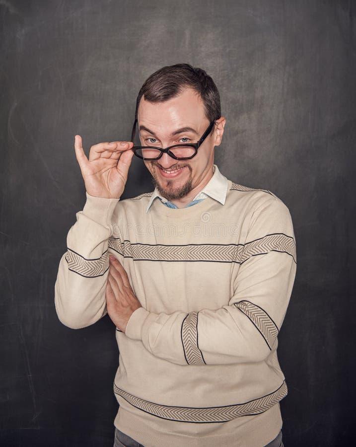Profesor divertido en las lentes que le miran en la pizarra imagenes de archivo