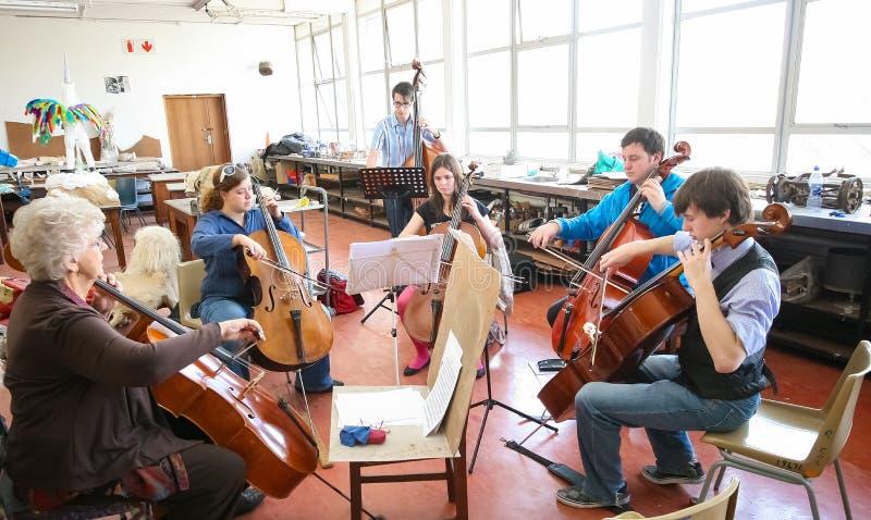 Profesor en la clase de la orquesta de la escuela de música foto de archivo
