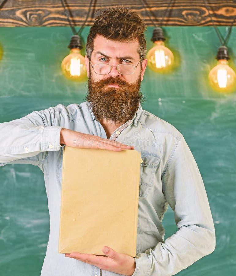 Profesor en las lentes que presentan el libro en blanco El inconformista barbudo sostiene el libro, pizarra en fondo literatura foto de archivo