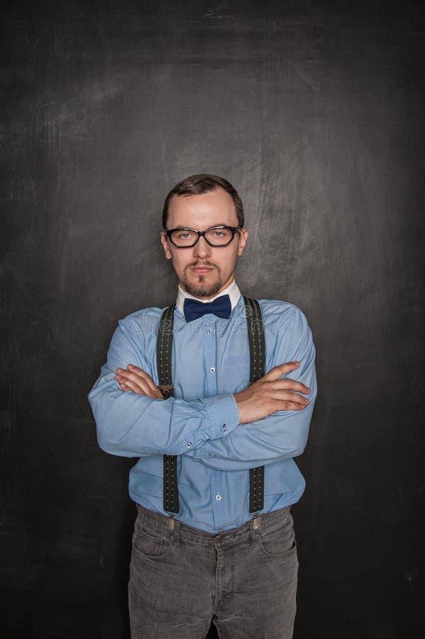 Profesor estricto hermoso en las lentes que le miran en la pizarra fotos de archivo