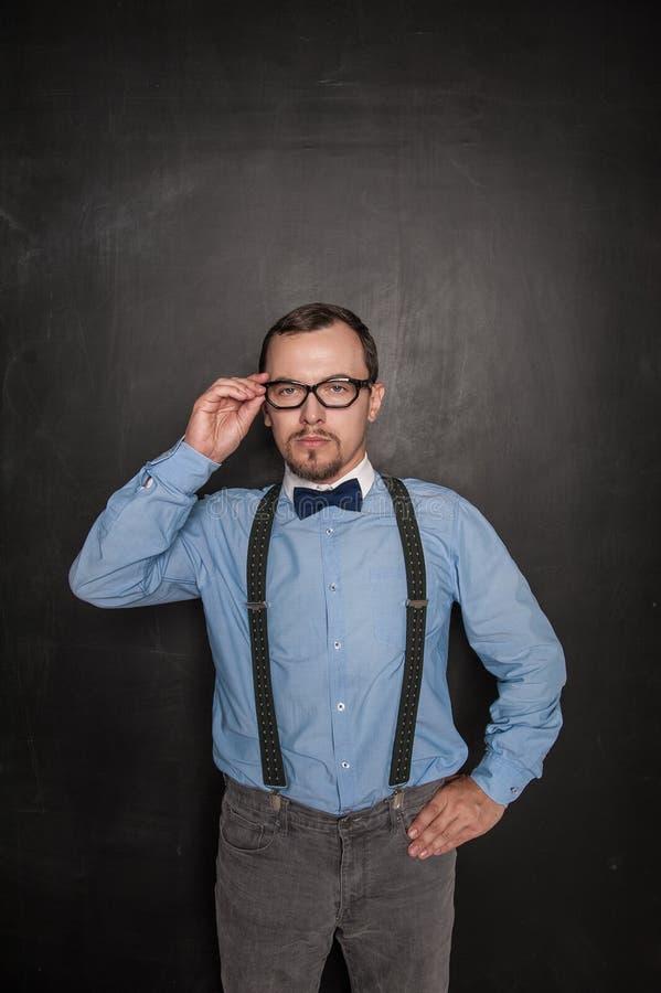 Profesor estricto hermoso en las lentes que le miran en la pizarra imagen de archivo libre de regalías