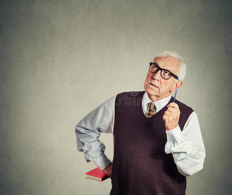 Profesor estricto mayor que sostiene el libro y la pluma, mirando para arriba fotos de archivo libres de regalías