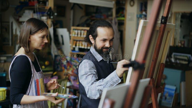 Profesor experto del artista que muestra y que discute fundamentos de la pintura al estudiante en la arte-clase fotos de archivo