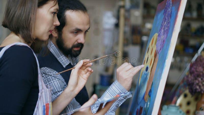 Profesor experto del artista que muestra y que discute fundamentos de la pintura al estudiante en la arte-clase imagen de archivo libre de regalías