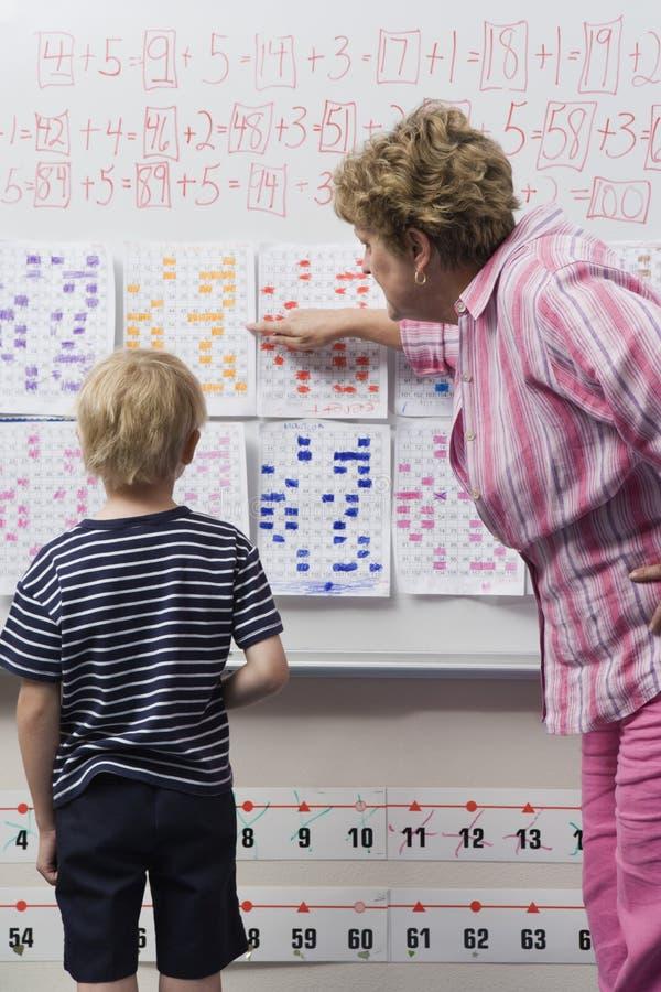 Profesor Explaining Calendar To Little Boy foto de archivo