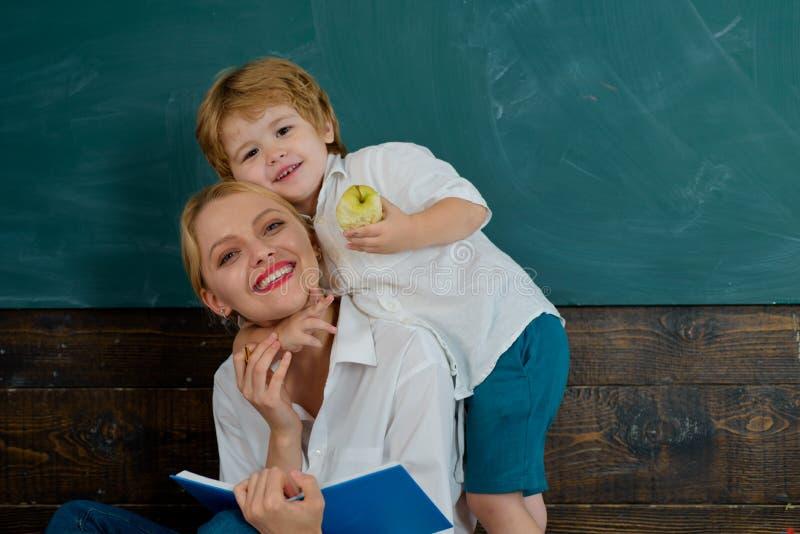 Profesor favorito. Joven profesor y feliz estudiante. Escuela y lectura. Libro interesante. Mamá e hijo estudian juntos fotografía de archivo libre de regalías