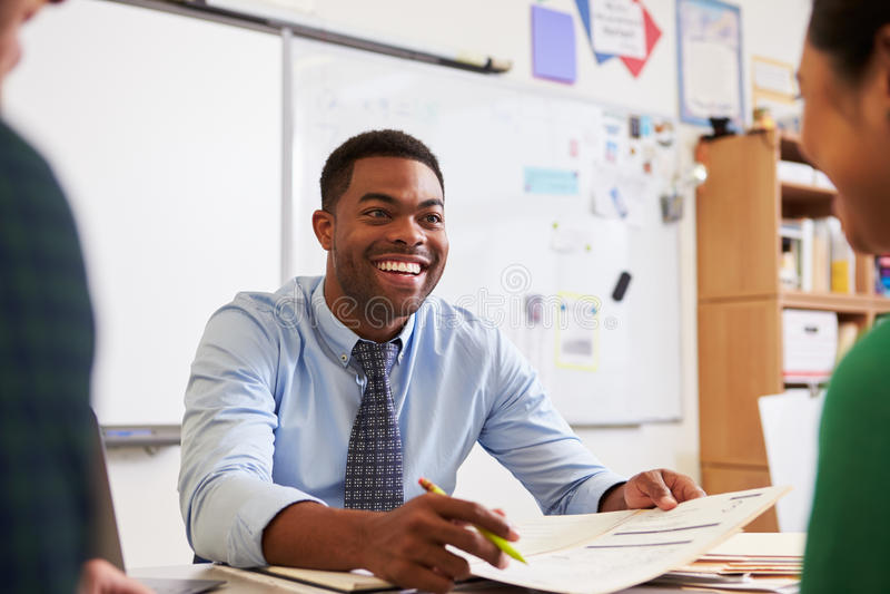 Profesor feliz en el escritorio que habla con los estudiantes de la enseñanza para adultos imagenes de archivo