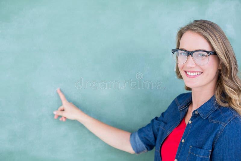 Profesor geeky sonriente que señala la pizarra fotografía de archivo