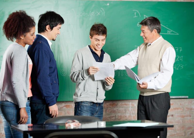 Profesor Giving Exam Result al estudiante At fotos de archivo