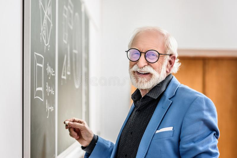 profesor gris sonriente del pelo que lleva a cabo el pedazo imagenes de archivo
