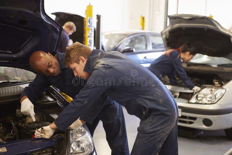 Profesor Helping Student Training a ser mecánicos de coche imagenes de archivo