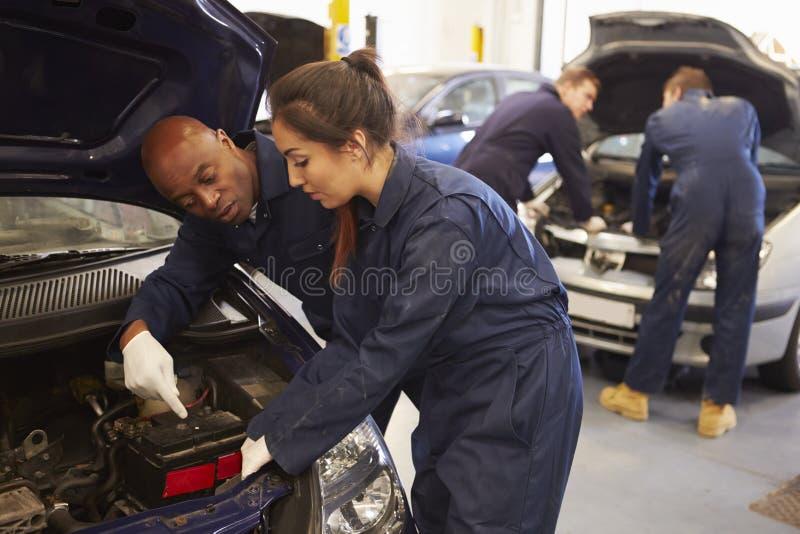 Profesor Helping Student Training a ser mecánicos de coche fotografía de archivo